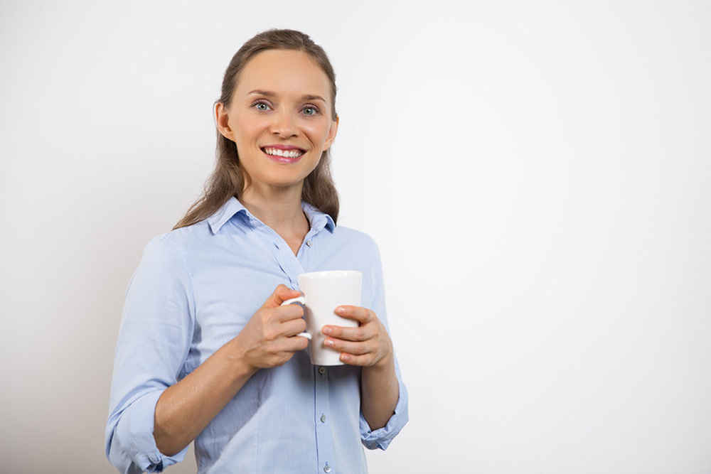 Closeup portrait of smiling at camera pretty young woman standing, holding mug and drinking tea or coffee. Isolated view on white background.